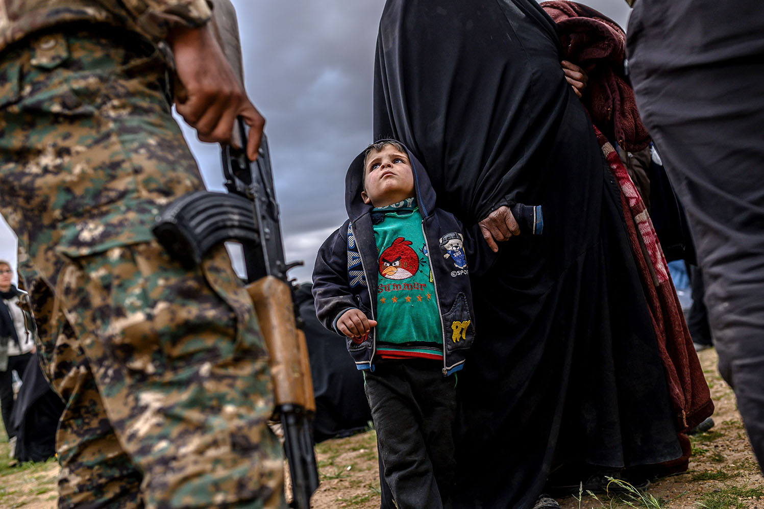 A young child looks at a member of the Kurdish-led Syrian Democratic Forces (after leaving the Islamic State group's last holdout of Baghouz in Syria's northern Deir Ezzor province on Feb. 27. BULENT KILIC/AFP/Getty Images