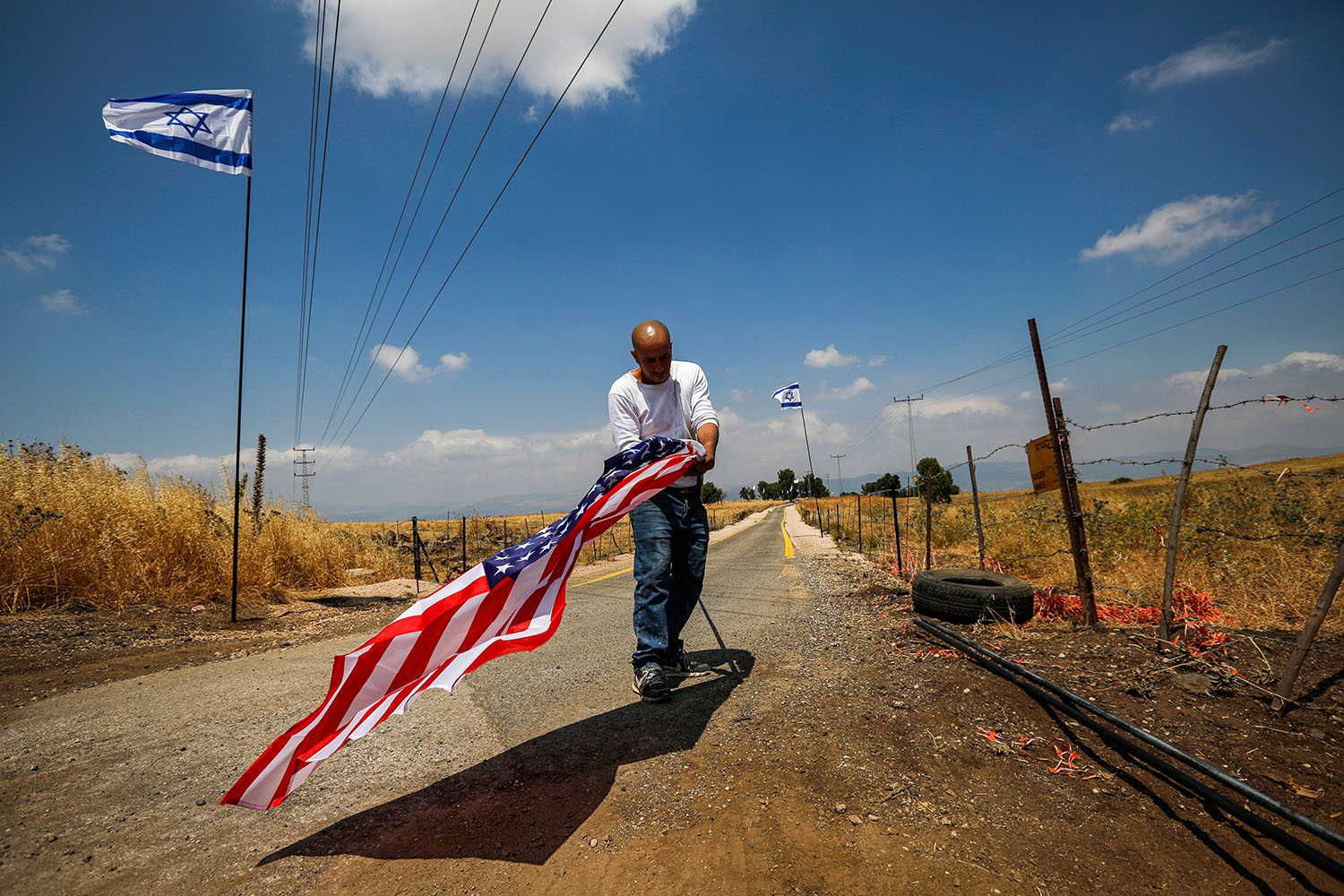 A worker attaches a U.S. flag to a mast before displaying it along the road with other Israeli flags in the settlement of Qela Bruchim in the Israeli-annexed Golan Heights on June 14. JALAA MAREY/AFP/Getty Images