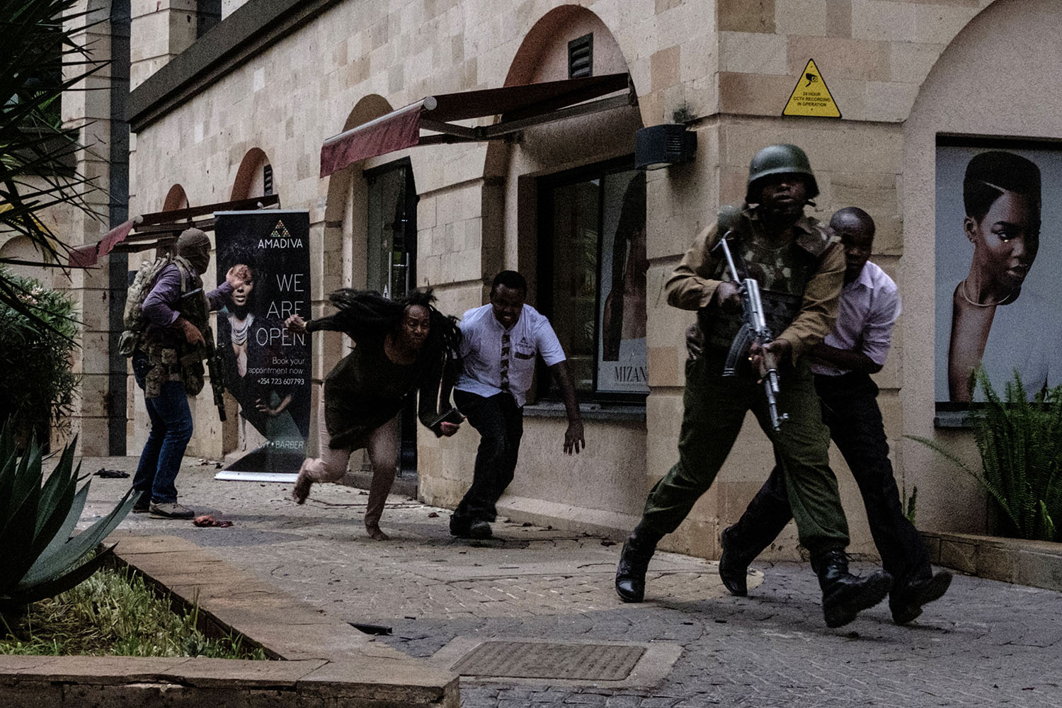 Kenyan security forces help people escape after a bomb blast at DusitD2 hotel in Nairobi on Jan. 15. A huge blast followed by a gun battle rocked the upmarfket hotel and office complex, killing at least 21 in an attack claimed by the al-Qaeda-linked al-Shabaab Islamist group. KABIR DHANJI/AFP/Getty Images