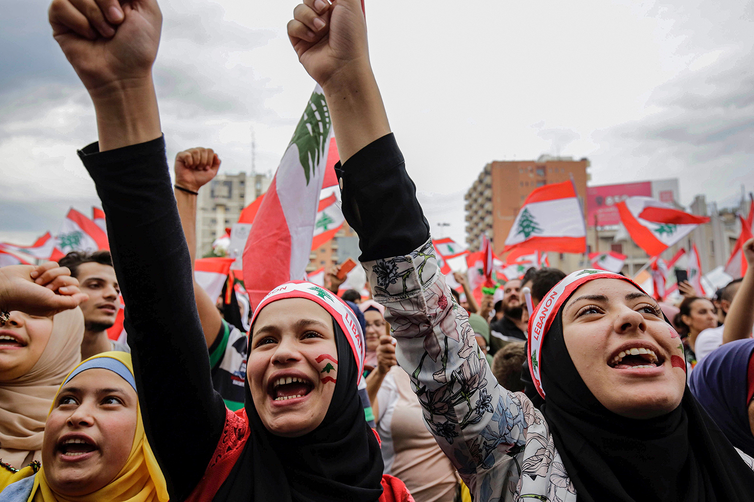 LEBANON | Women wearing bandanas showing the Lebanese national flag chant slogans during a demonstration against tax increases and offical corruption in Tripoli on Oct. 23. IBRAHIM CHALHOUB/AFP via Getty Images