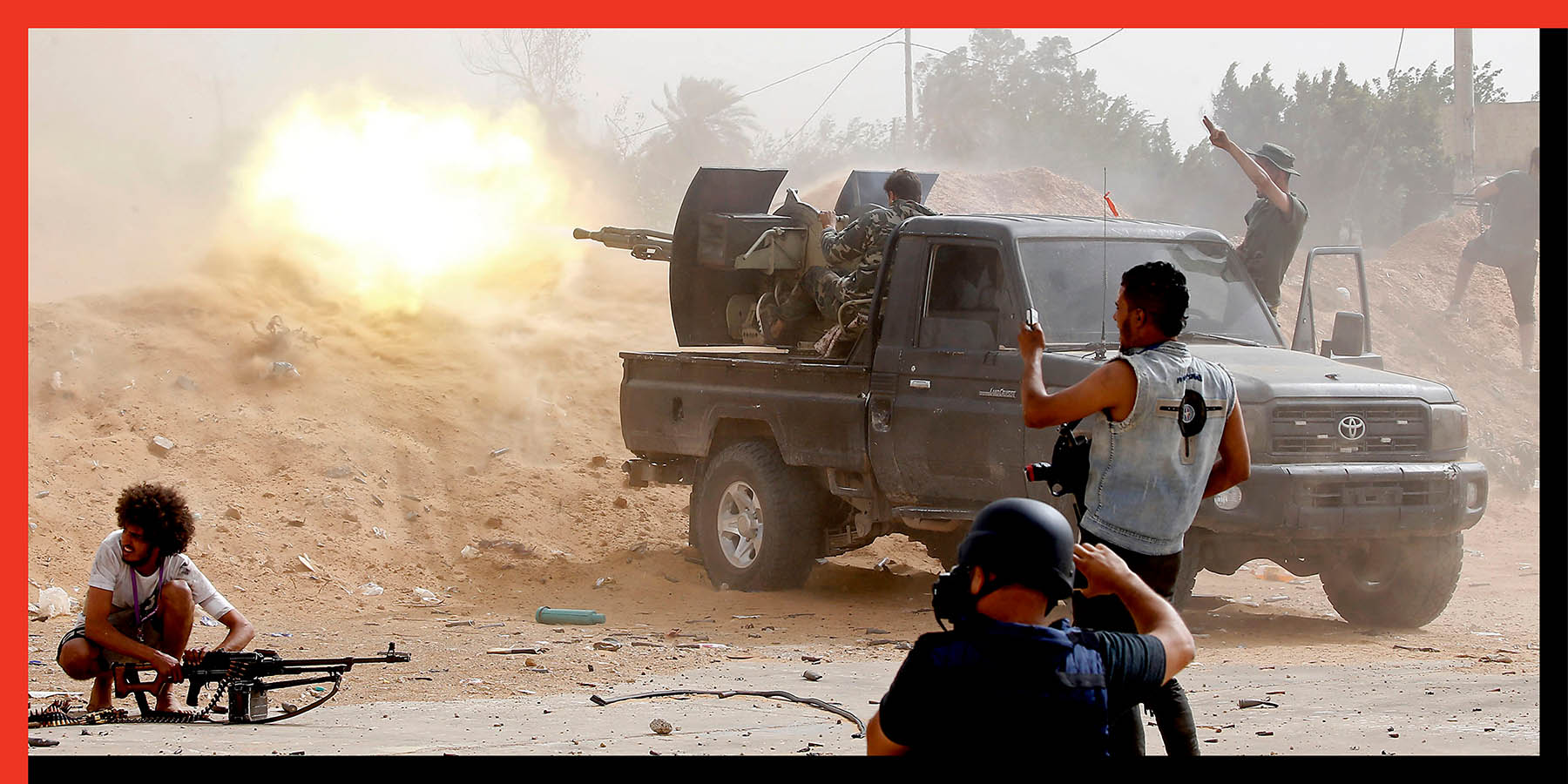 A fighter loyal to the Libyan Government of National Accord fires a machine gun as a photographer take pictures of the scene during clashes against forces loyal to Libya strongman Khalifa Haftar south of Tripoli on May 25.
