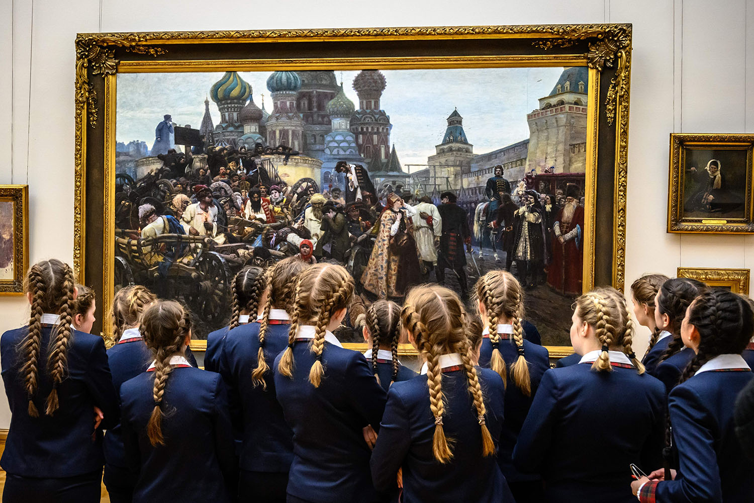 """Schoolgirls look at """"The Morning of the Streltsy Execution"""" by Russian painter Vasily Surikov at The State Tretyakov Gallery in Moscow on Feb. 26. MLADEN ANTONOV/AFP/Getty Images"""