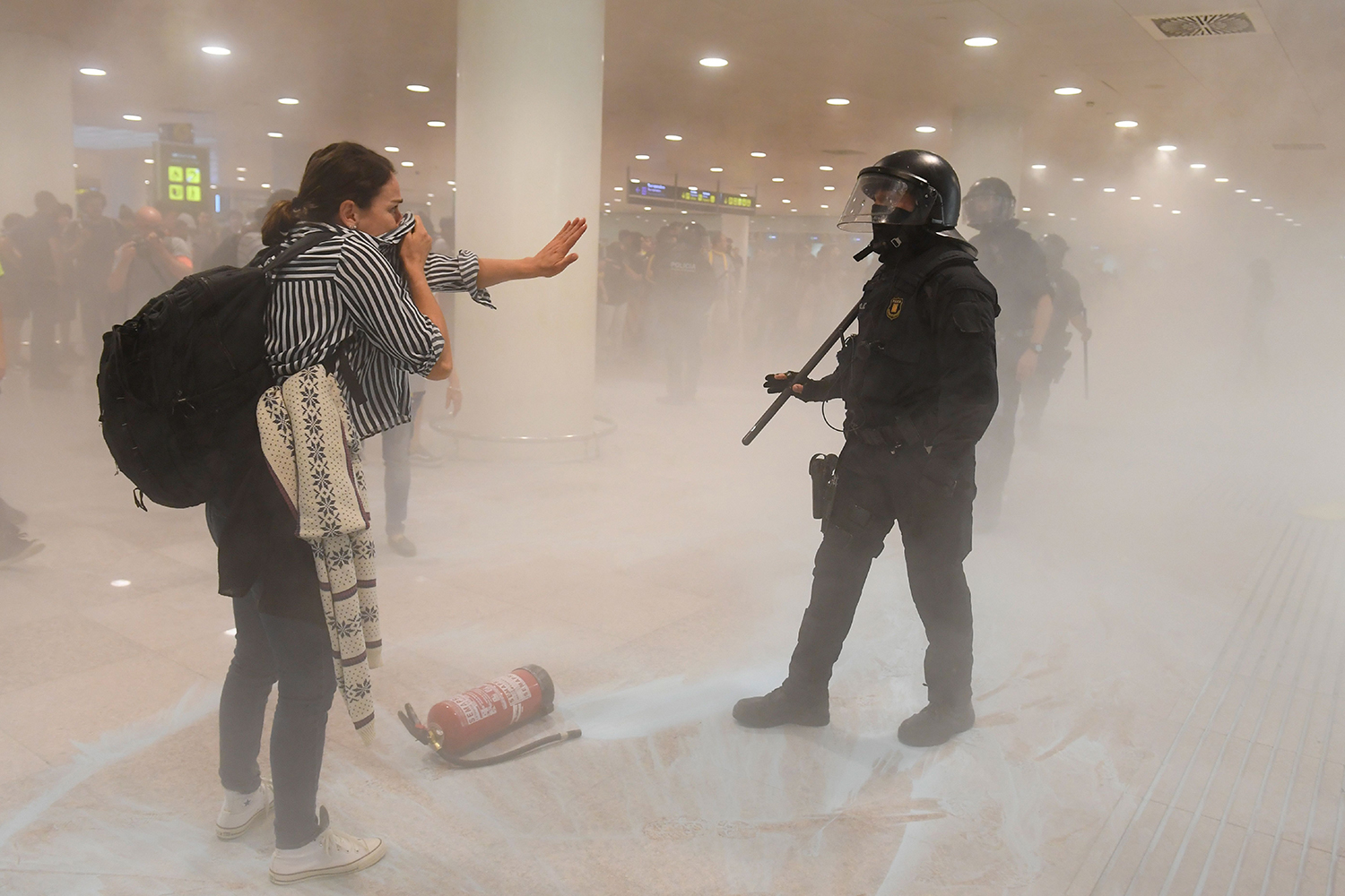 SPAIN | A protester protects her face in front of a policemen inside El Prat airport in Barcelona on Oct. 14, as thousands took to the streets after Spain's Supreme Court sentenced nine Catalan separatist leaders to between nine and 13 years in jail for sedition over the failed 2017 independence bid. JOSEP LAGO/AFP via Getty Images