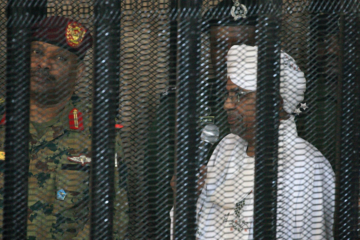 Sudan's deposed ruler Omar al-Bashir stands in a defendant's cage during the opening of his cor-ruption trial in Khartoum on Aug. 19.