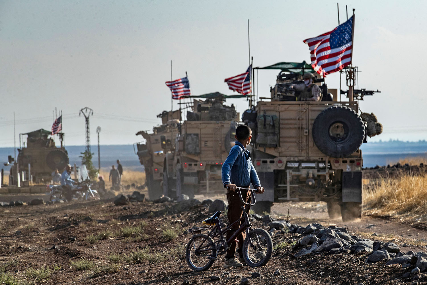 A Syrian boy on his bicycle looks at a convoy of U.S. armored vehicles patrolling fields near the northeastern town of Qahtaniyah at the border with Turkey on Oct. 31. DELIL SOULEIMAN/AFP via Getty Images