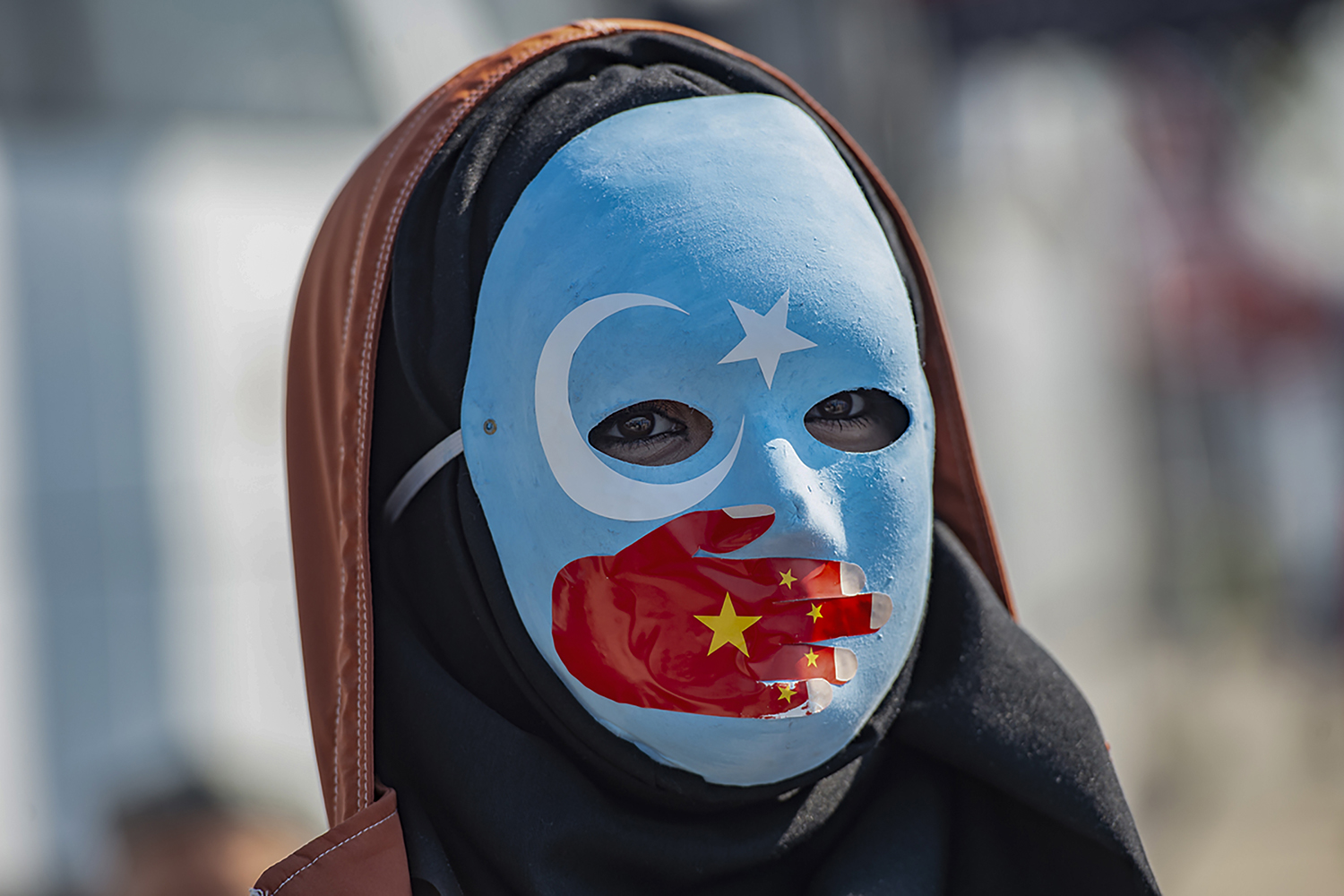 TURKEY | A demonstrator wears a mask painted with the colors of the flag of East Turkestan and a hand bearing the colours of the Chinese flag as she joins supporters of China's Muslim Uighur minority and Turkish nationalists during a protest in front of the Chinese consulate in Istanbul on Oct. 1. YASIN AKGUL/AFP via Getty Images