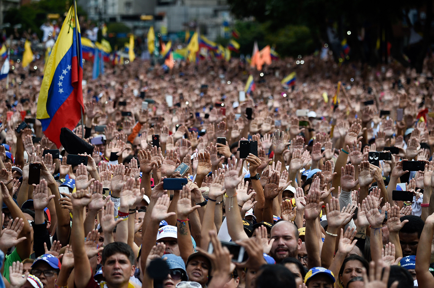 VENEZUELA | People raise their hands during a mass opposition rally against President Nicolas Maduro in Caracas on Jan. 23. FEDERICO PARRA/AFP via Getty Images