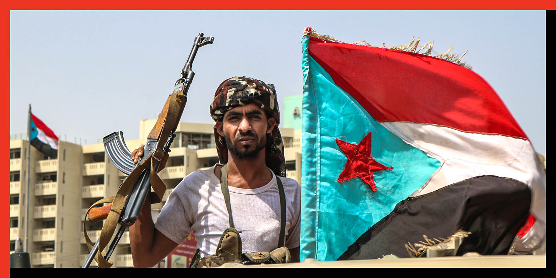 A fighter poses with a Kalashnikov assault rifle and the southern separatist flag (the old flag of South Yemen) in the Khor Maksar district of Aden on Aug. 29.