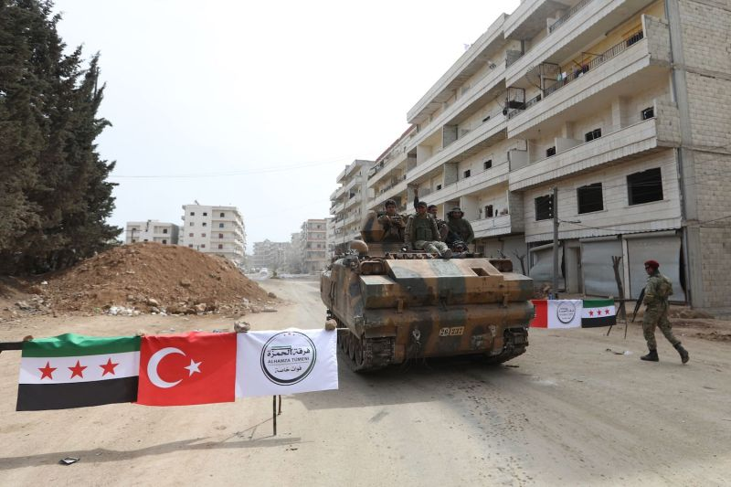 Turkish-backed Syrian Arab fighters man a checkpoint in the Kurdish-majority city of Afrin in northern Syria after seizing control of it from the Kurdish People's Protection Units (YPG) on March 18, 2018.