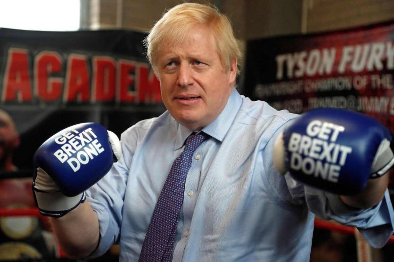 "British Prime Minister Boris Johnson wears boxing gloves emblazoned with ""Get Brexit Done"" as he poses for a photograph at Jimmy Egan's Boxing Academy in Manchester, England on Nov. 19."