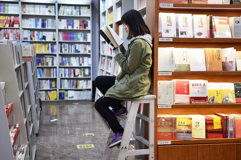 A woman reads a book in a bookstore in Beijing on Nov. 7, 2017.