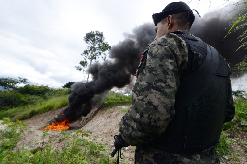 A soldier stands guard as cocaine seized on the Atlantic coast of Honduras is incinerated on October 17, 2013.