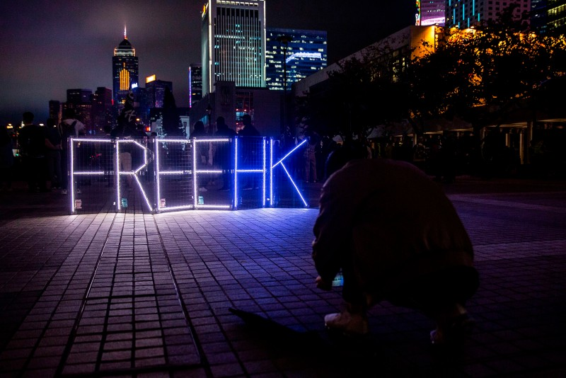 """Pro-democracy protesters take photos of a """"Free HK"""" light display in Edinburgh Place in central Hong Kong on Dec. 30."""
