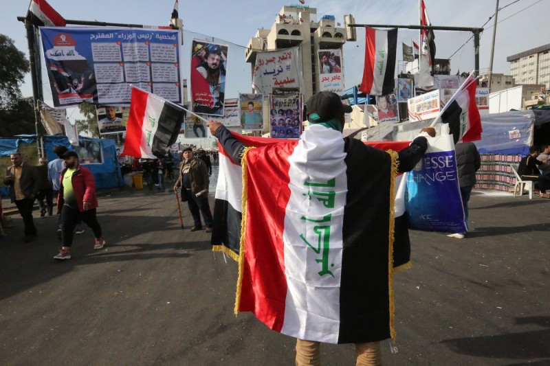 An Iraqi protester clad with the national flag takes part in anti-government demonstrations at Tahrir square in the capital Baghdad, on Dec. 30.
