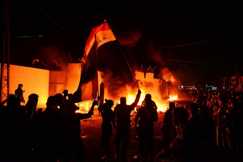 Iraqi demonstrators gather as flames consume Iran's consulate in Najaf, Iraq, on Nov. 27.