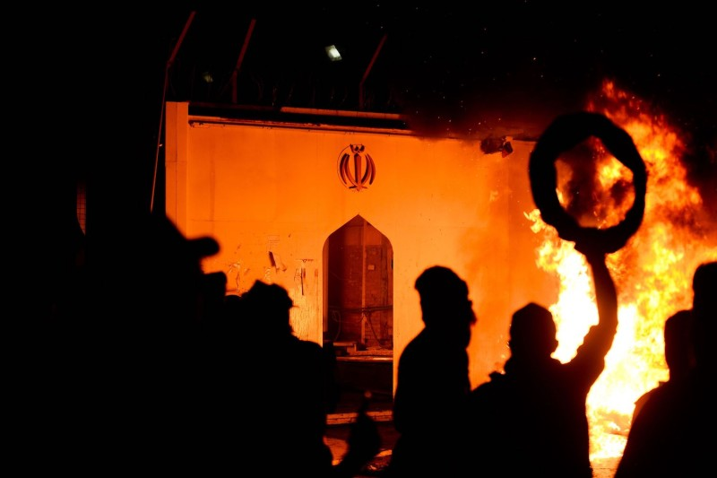 Iraqi demonstrators gather as flames consume Iran's consulate in the Iraqi Shiite holy city of Najaf on Nov. 27.