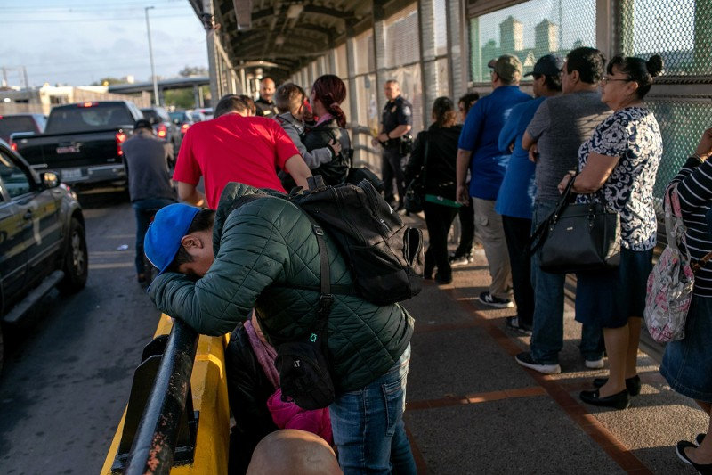 A Mexican asylum seeker  waits with his family on the international bridge from Mexico to the United States on Dec. 9.