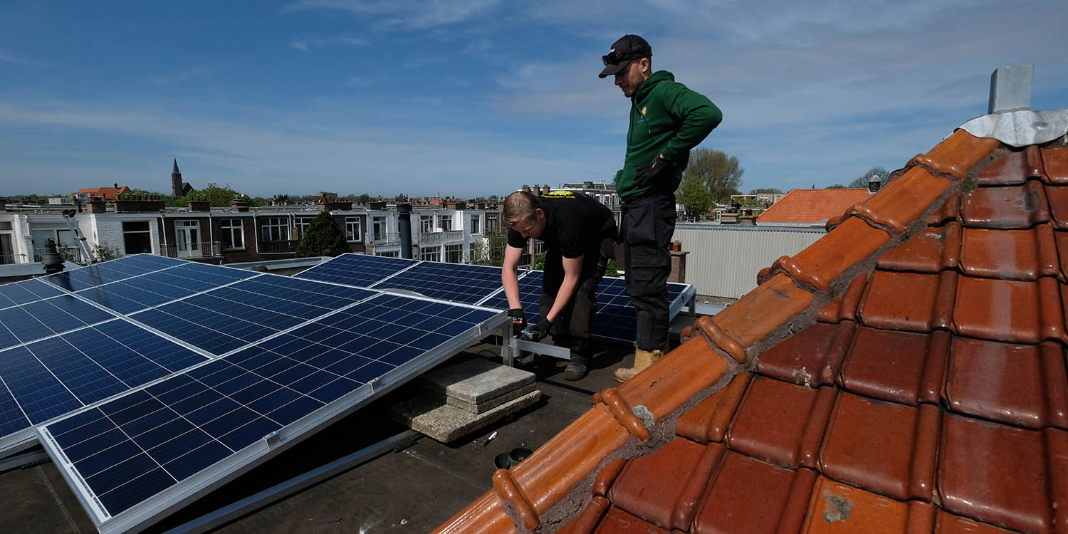 Workers install solar panels atop a house in The Hague, Netherlands, on April 23, 2018.