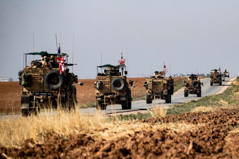 A convoy of U.S. armored vehicles patrols the northeastern town of Qahtaniyah, Syria.