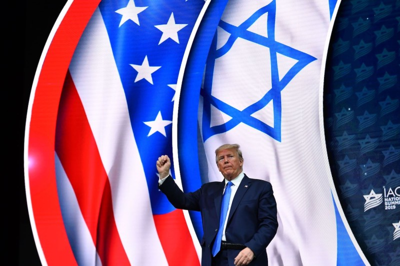U.S. President Donald Trump stands on stage after his address to the Israeli American Council National Summit 2019.
