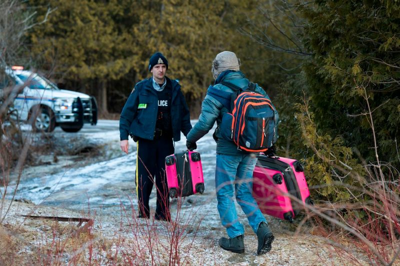 A man faces a member of the Canadian police as he carries baggage as he crosses the U.S.-Canada border on Feb. 26, 2017, in  Champlain, New York.