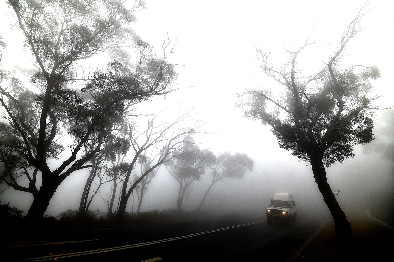 A car makes its way through thick fog mixed with bushfire smoke in the Ruined Castle area of the Blue Mountains on Jan. 11 SAEED KHAN/AFP via Getty Images
