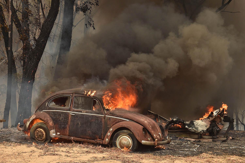 An old car burns from bushfires in Balmoral, southwest of Sydney, on Dec. 19. PETER PARKS/AFP via Getty Images