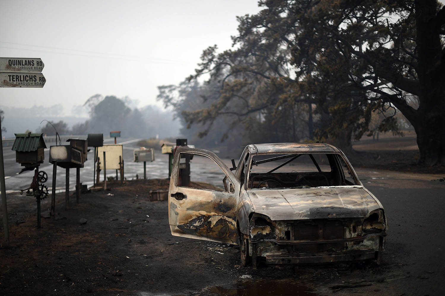 A burned vehicle is seen on Quinlans street after an overnight bushfire in Quaama on Jan. 6. SAEED KHAN/AFP via Getty Images