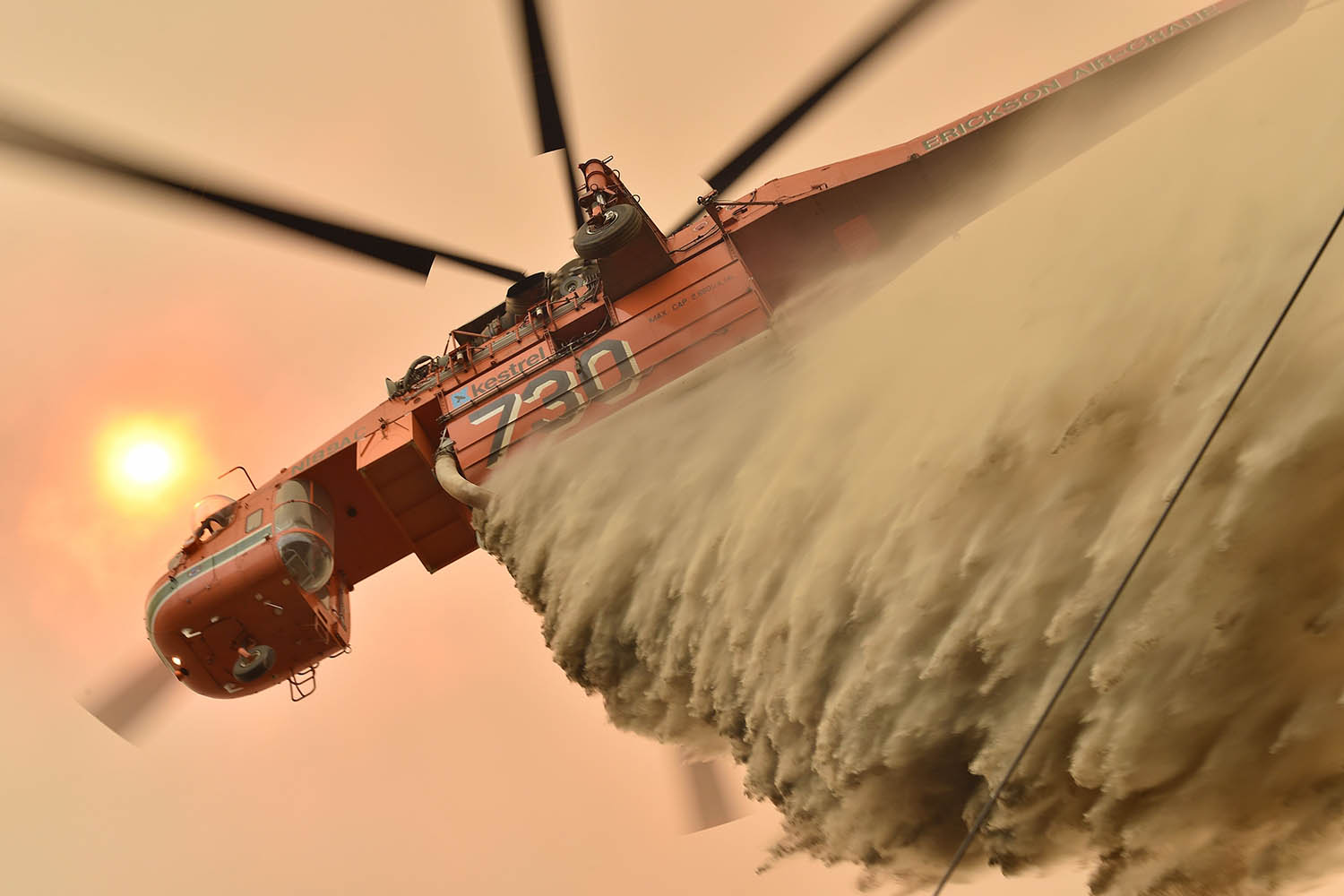 A helicopter drops fire retardant to protect a property in Balmoral, about 100 miles southwest of Sydney, on Dec. 19. PETER PARKS/AFP via Getty Images