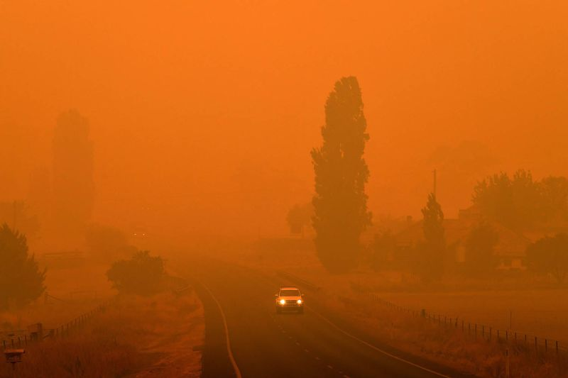 Residents commute on a road through thick smoke from bushfires in Bemboka, in Australia's New South Wales state, on Jan. 5. SAEED KHAN/AFP via Getty Images)