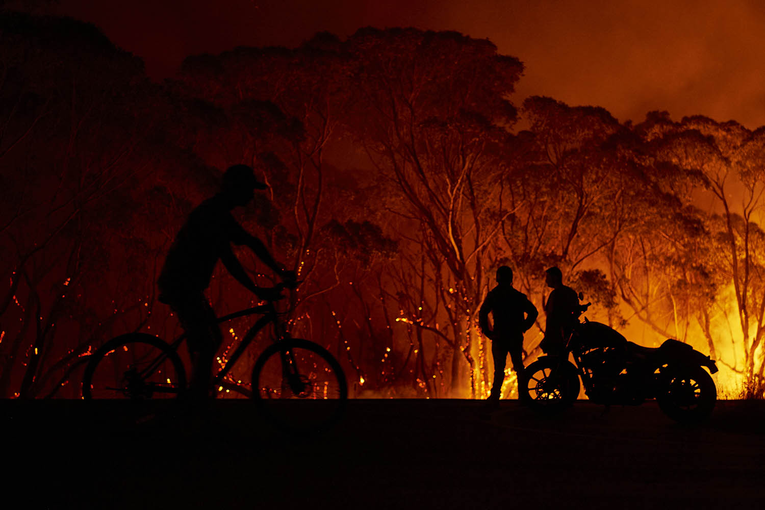 Residents watch as flames burn through bush in Lake Tabourie on on Jan. 4. Brett Hemmings/Getty Images