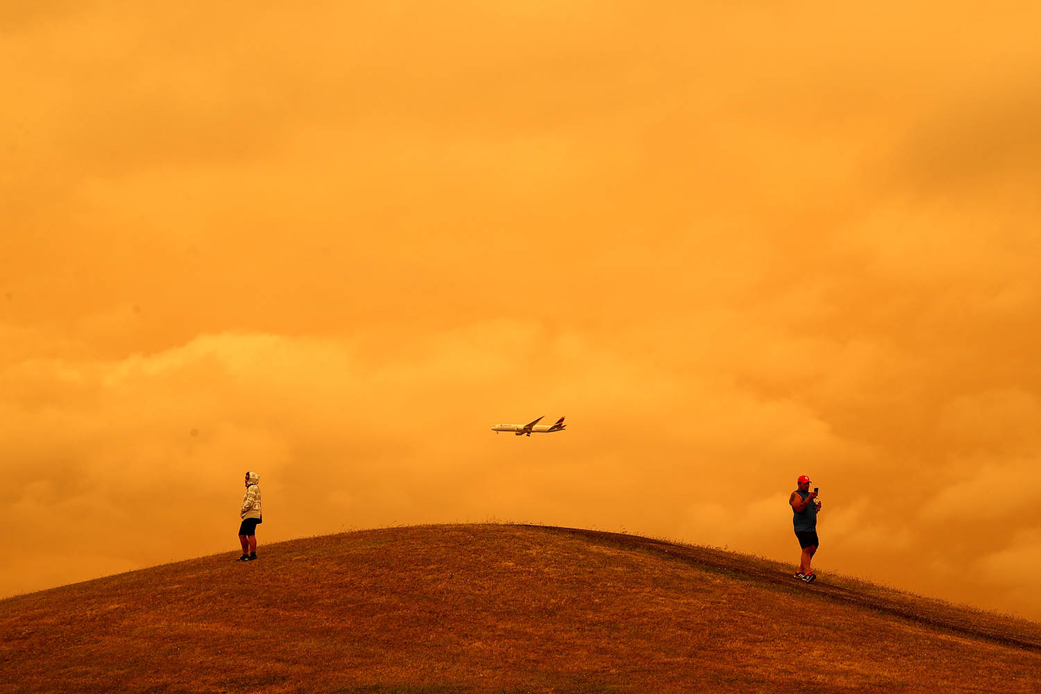 A plane flies through orange skies from the Australian fires over Manukau as seen from Totara Park in Auckland, New Zealand, on Jan. 5. Phil Walter/Getty Images