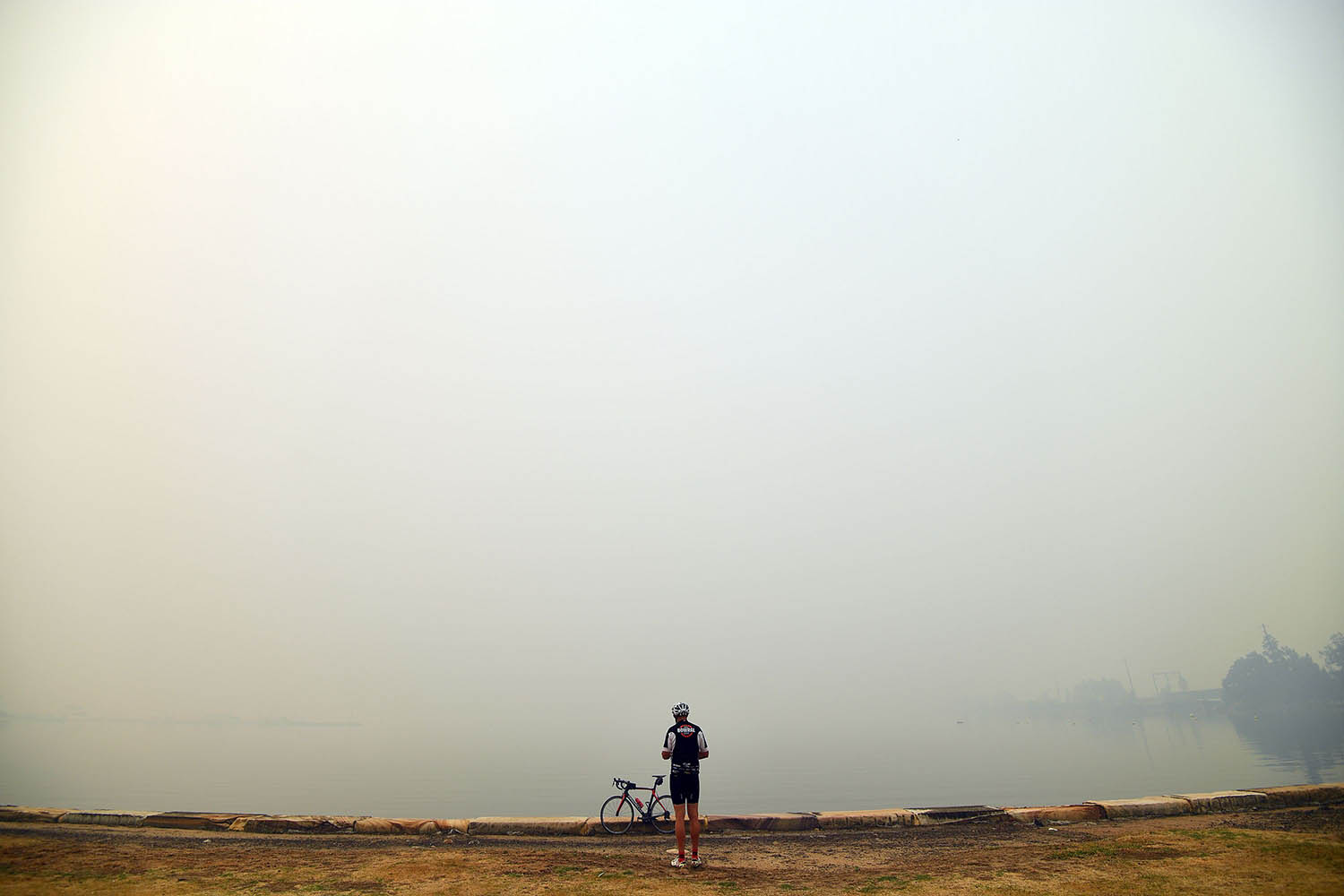 A cyclist takes pictures of thick smoke from bushfires in Gosford, north of Sydney, on Dec. 10. SAEED KHAN/AFP via Getty Images