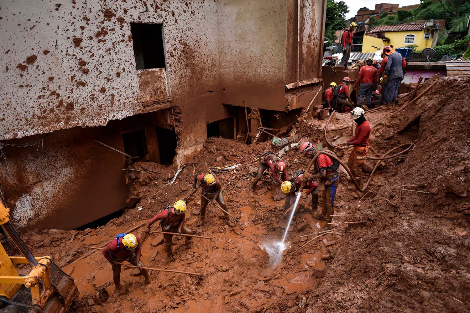 Firefighters search for missing people using a hydraulic dismantling technique, which uses water to disperse mud, after a landslide in Vila Bernadete, Brazil, on Jan. 26. A landslide buried several houses in Vila Bernadete, leaving four dead and seven missing. DOUGLAS MAGNO/AFP via Getty Images