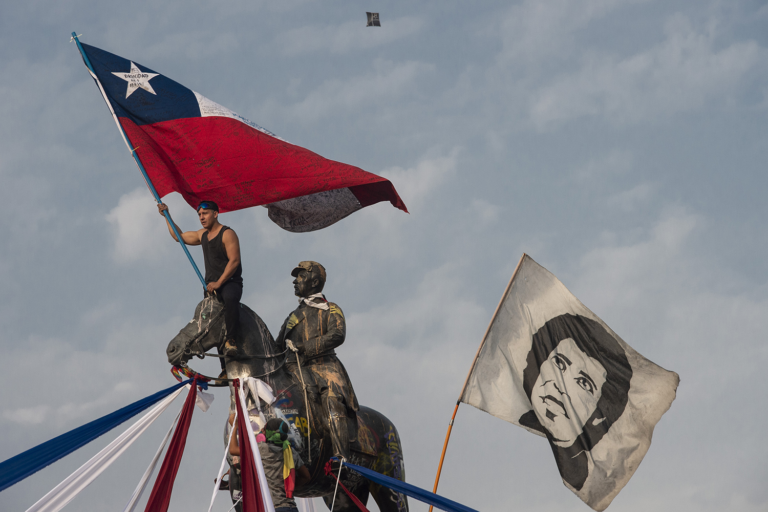 A demonstrator waves a Chilean flag next to another flag depicting late Chilean musician Victor Jara during a protest against President Sebastian Pinera's government, in Santiago on Jan. 17. MARTIN BERNETTI/AFP via Getty Images
