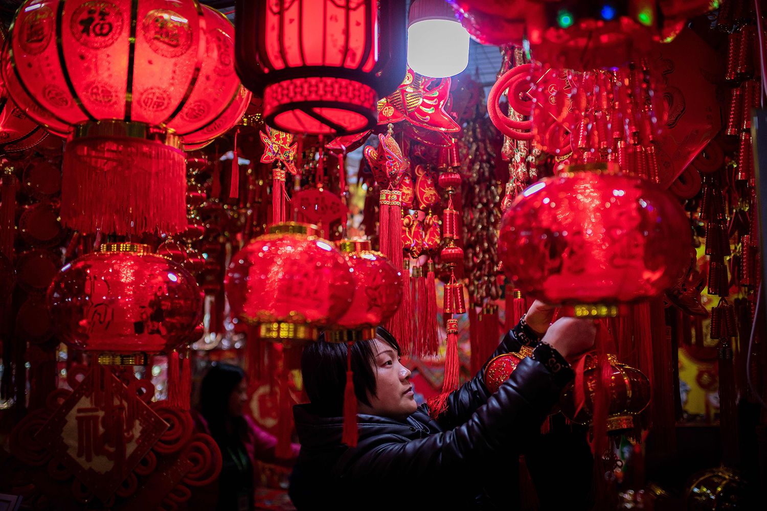 A vendor adjusts lanterns at her stall at a market in Beijing on Jan. 15 ahead of the Lunar New Year of the Rat. NICOLAS ASFOURI/AFP via Getty Images
