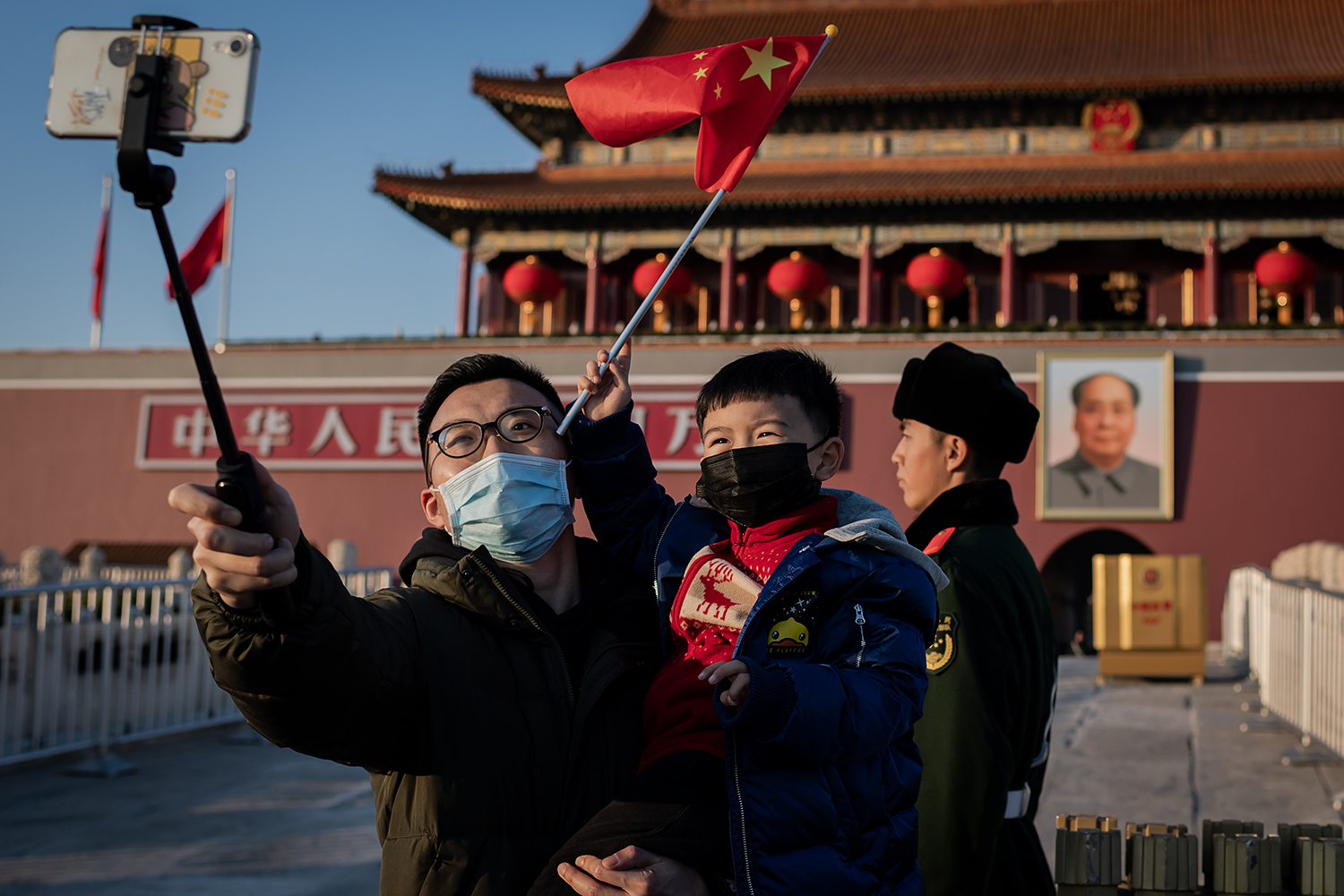 A boy and his father wear protective masks amid the coronavirus outbreak as they take a selfie at Tiananmen Gate in Beijing on Jan. 23. NICOLAS ASFOURI/AFP via Getty Images