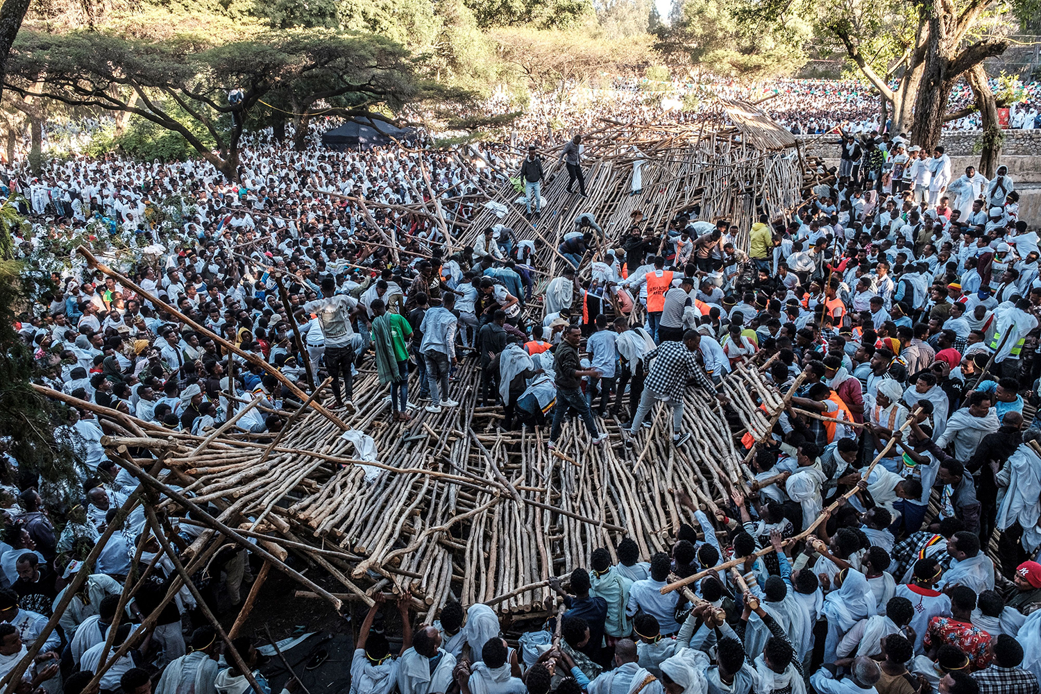 A crowd removes the scaffolding of a structure that collapsed during the celebration of Timkat, the Ethiopian Epiphany, in Gondar on Jan. 20. At least 10 people were killed and about 100 injured when the platform on which they sat while attending the Orthodox Epiphany Festival collapsed. EDUARDO SOTERAS/AFP via Getty Images