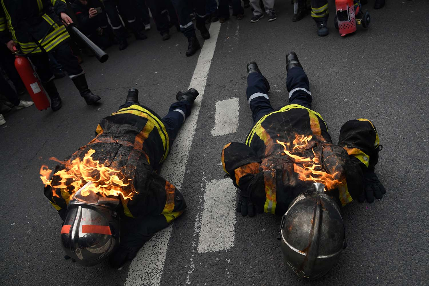 Two firefighters set alight lie on the ground as another prepares to extinguish them as they take part in a demonstration to protest the French government's plan to overhaul the country's retirement system in Paris, on Jan. 28. BERTRAND GUAY/AFP via Getty Images
