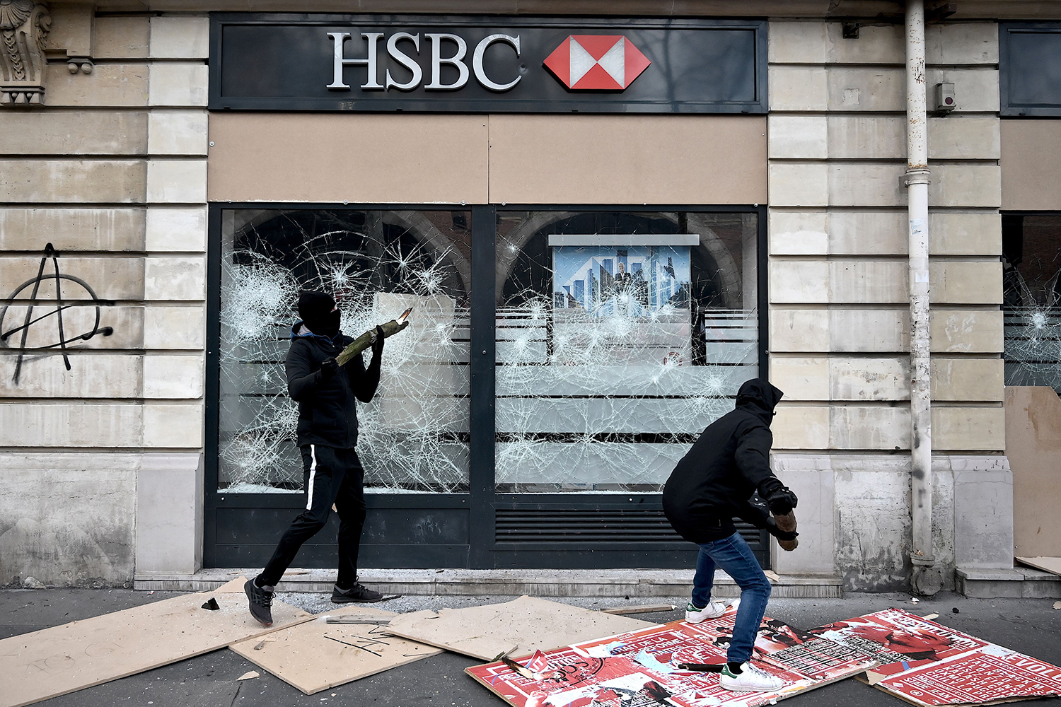 Two men break the windows of a branch of the HSBC bank during a demonstration in Paris on Jan. 11 as part as a nationwide multi-sector strike against the French government's pensions overhaul. LIONEL BONAVENTURE/AFP via Getty Images