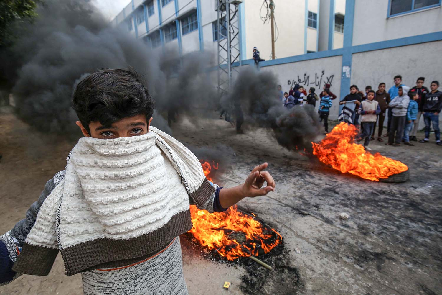 A young Palestinian protester stands in front of burning tires during demonstrations against a U.S.-brokered Mideast peace plan in Khan Yunis in the southern Gaza Strip, on Jan. 29. SAID KHATIB/AFP via Getty Images