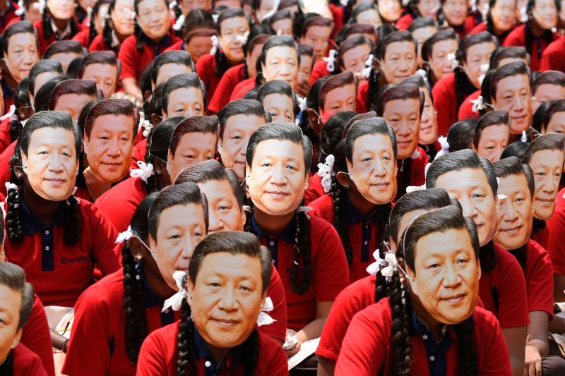 Indian students wear masks of China's President Xi Jinping