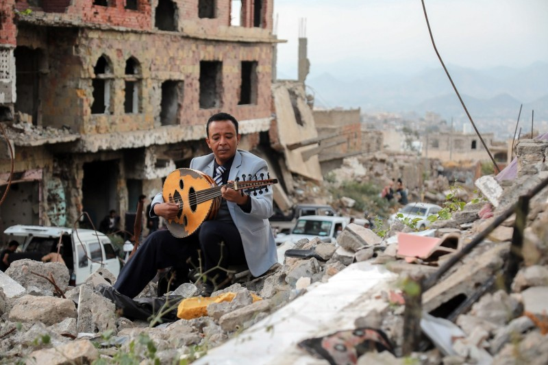 A Yemeni artist sitting atop the rubble of a collapsed buiding, plays the aoud during a street performance in Yemen's third city of Taez, on December 6, 2019.