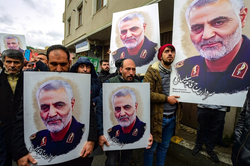 Protesters hold pictures of Iranian commander Qassem Suleimani