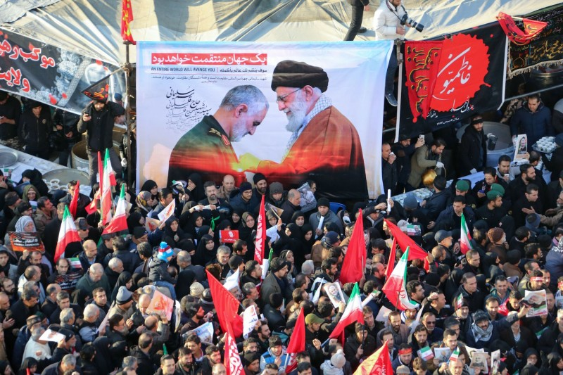 Iranian mourners carry a picture of Supreme Leader Ayatollah Ali Khamenei decorating now-slain Gen. Qassem Suleimani during his funeral procession in Tehran on Jan. 6.