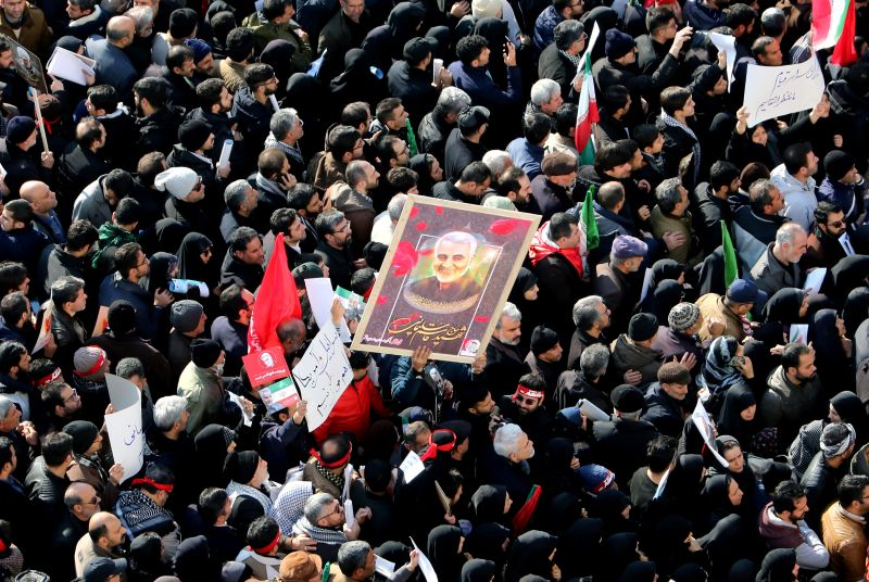 Iranian mourners lift a picture of slain military commander Qassem Suleimani during a funeral procession in Tehran on Jan. 6.