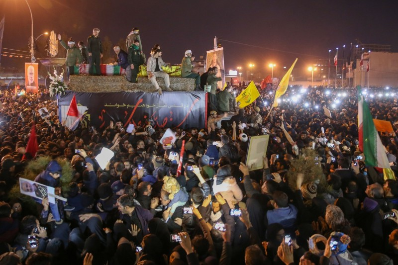 Iranians gather around a vehicle carrying the caskets of the slain military commander Qassem Suleimani and others during a funeral procession in the northern city of Qom on Jan. 6.