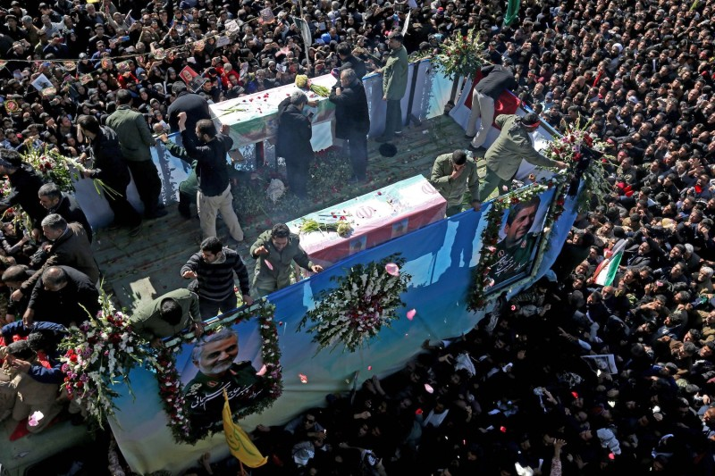 Iranian mourners gather around a vehicle carrying the coffin of slain general Qassem Suleimani