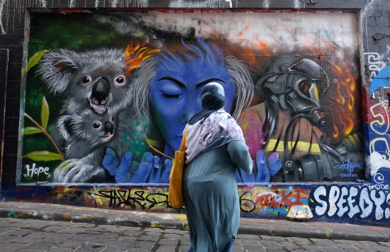 A woman walks past a mural depicting a koala and firefighters in Melbourne, Australia