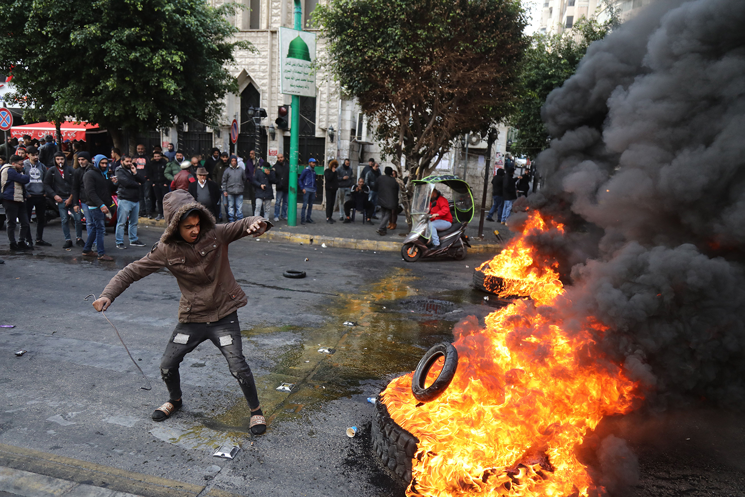 A Lebanese protester throws a tire on a burning pile blocking the road in Beirut on Jan. 22. IBRAHIM AMRO/AFP via Getty Images